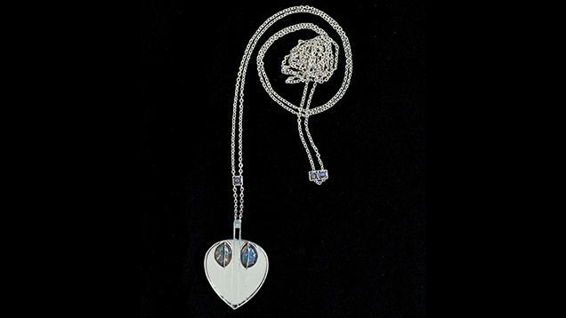Silberne Halskette mit herzfˆrmigem Anh‰nger, in diesem vor einem Spiegel zwei Opale in einer Verzierung aus senkrechten silbernen Stegen, um 1905. Silver necklace with a heart-spaped pendant, around 1905.